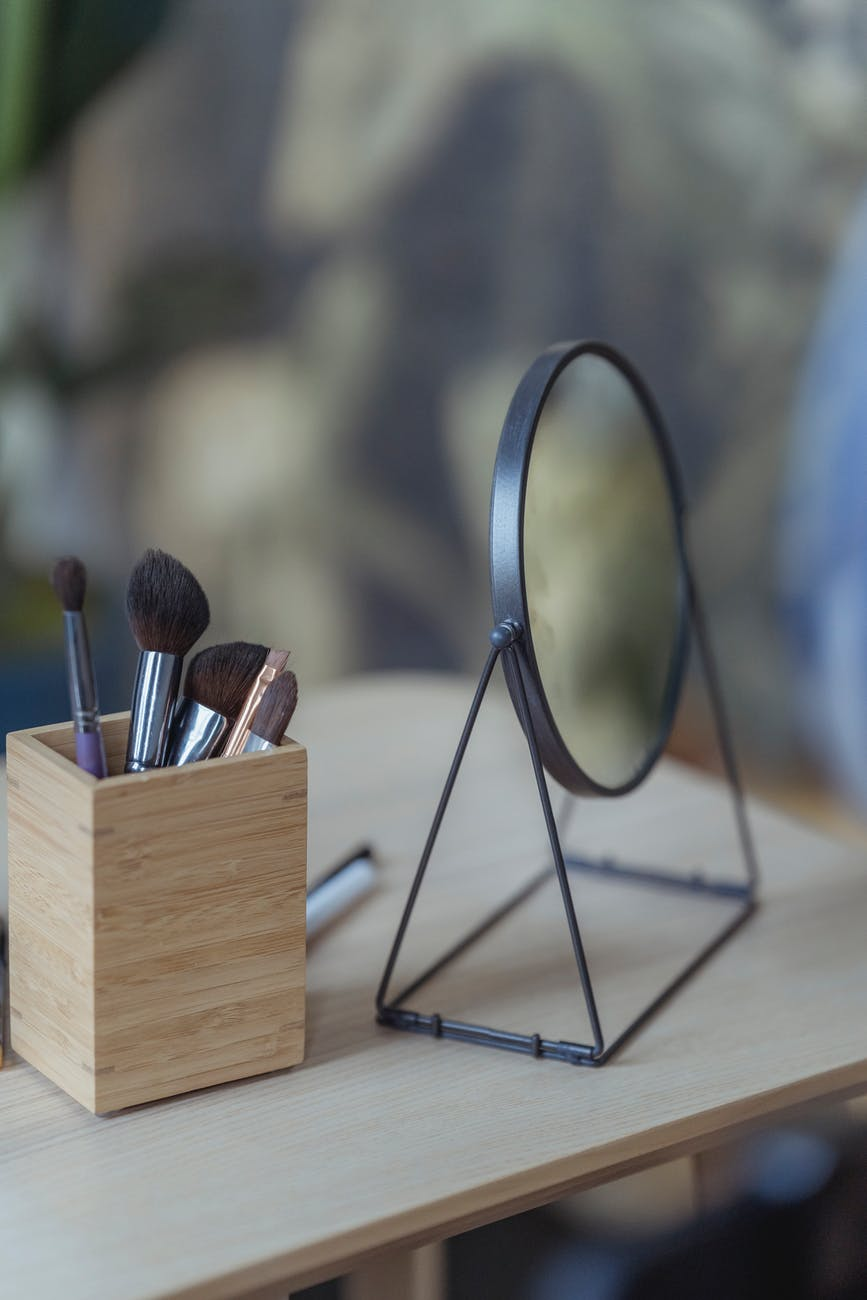 cosmetic brushes and round mirror placed on wooden table