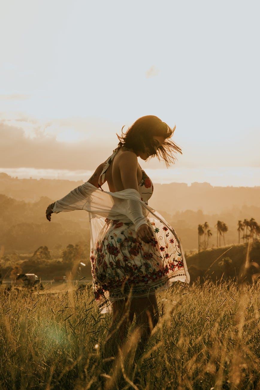 anonymous woman walking in grassy field